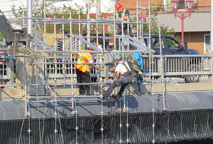 Men fixing bridge on scaffolding